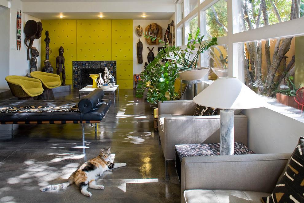 Foto di un soggiorno eclettico con pareti gialle, pavimento in cemento e camino classico