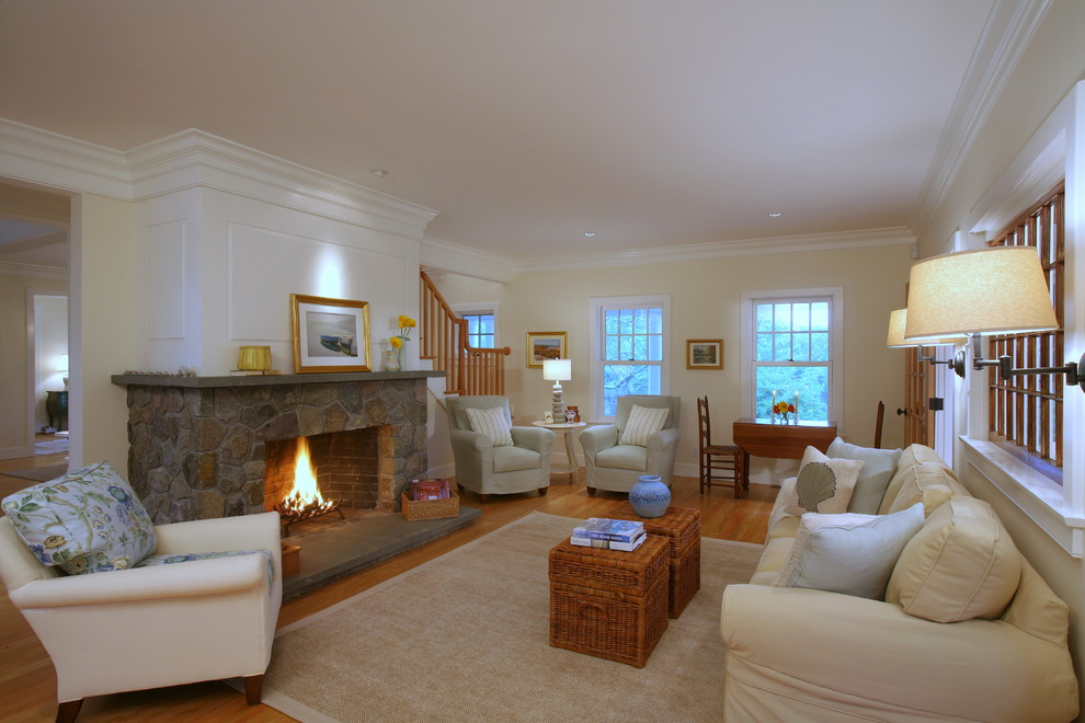 Example of a large classic open concept medium tone wood floor living room design in Boston with a stone fireplace, beige walls and a standard fireplace