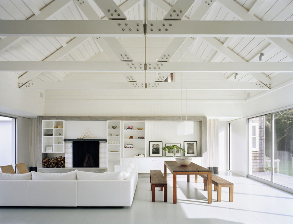 Huge trendy white floor living room photo in New York with white walls and a brick fireplace