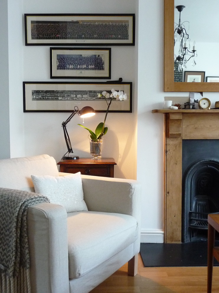 Eclectic medium tone wood floor living room photo in London with white walls and a standard fireplace