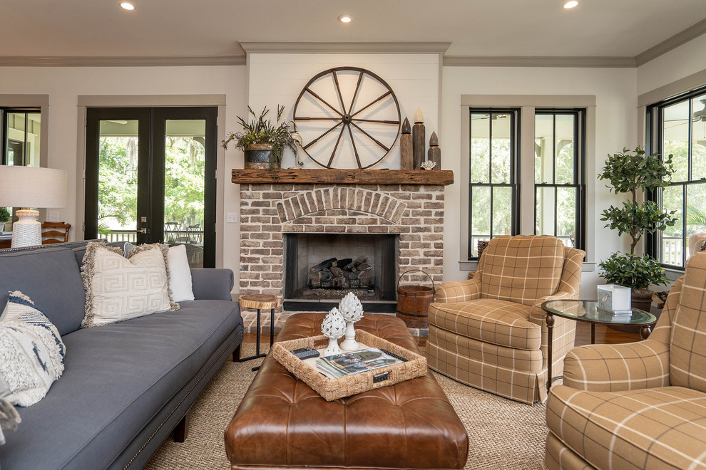 Inspiration for a country open concept medium tone wood floor and brown floor living room remodel in Atlanta with white walls, a standard fireplace and a brick fireplace