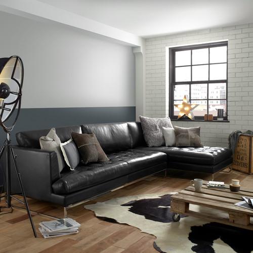 salon avec matériaux bruts, canapé en cuir noir et table basse en palette