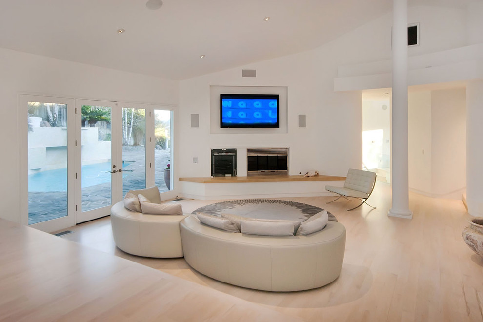 Inspiration for a modern living room remodel in San Francisco with white walls, a standard fireplace and a media wall