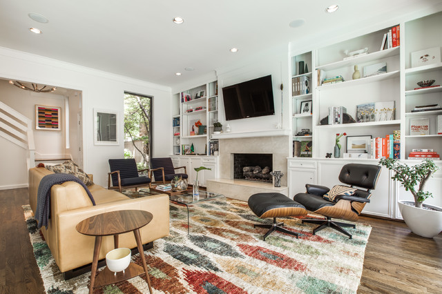This is an example of a transitional living room in Dallas with white walls, dark hardwood floors, a standard fireplace and a wall-mounted tv.