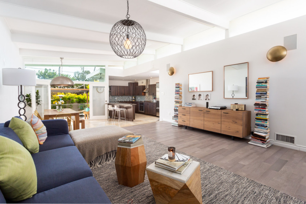 Living room - mid-sized 1950s open concept light wood floor, gray floor and exposed beam living room idea in Los Angeles with white walls and a corner fireplace