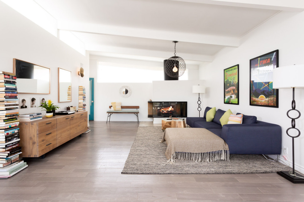 Inspiration for a mid-sized mid-century modern open concept light wood floor, gray floor and exposed beam living room remodel in Los Angeles with white walls and a corner fireplace