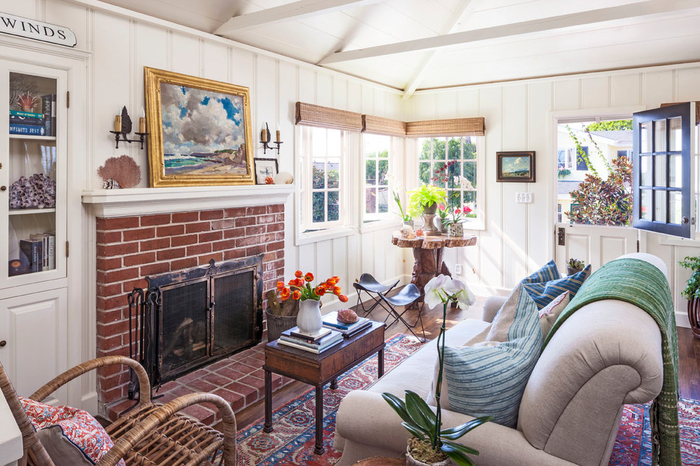 Example of a small beach style formal and enclosed dark wood floor living room design in Orange County with white walls, a standard fireplace and a brick fireplace
