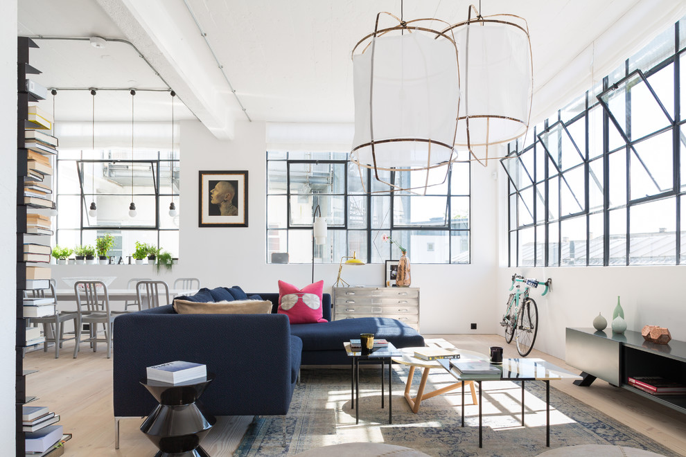 Example of a danish formal and open concept light wood floor living room design in London with white walls