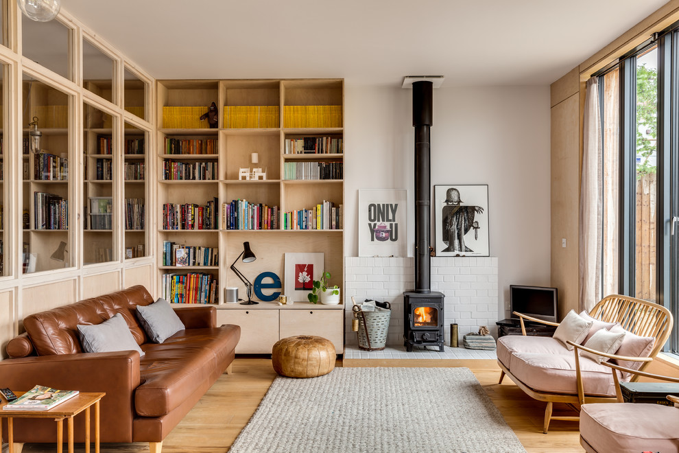 Example of a mid-sized danish open concept light wood floor living room design in London with white walls and a wood stove