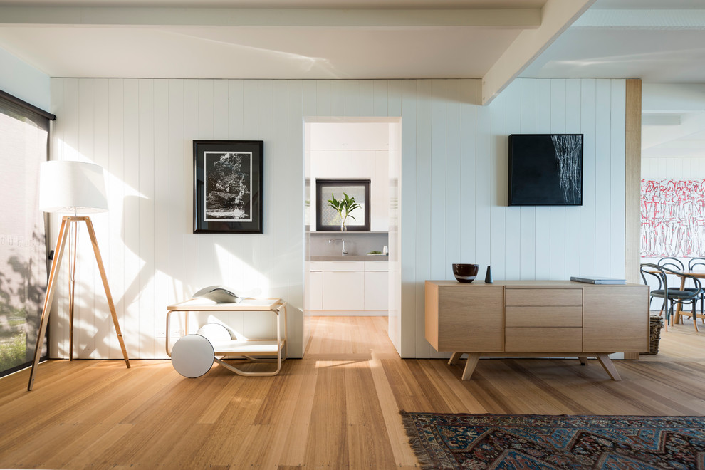 Mid-sized danish open concept medium tone wood floor living room photo in Melbourne with white walls