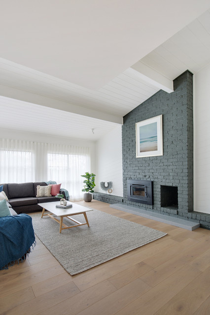 Photo of a large contemporary open concept living room in Sydney with white walls, limestone floors, a standard fireplace, a brick fireplace surround and beige floor.