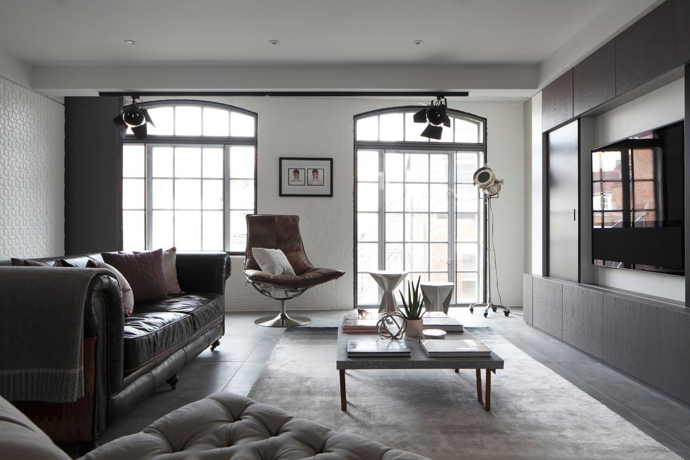 Imagen de salón para visitas abierto, industrial, de tamaño medio, con suelo de cemento, televisor colgado en la pared y paredes blancas
