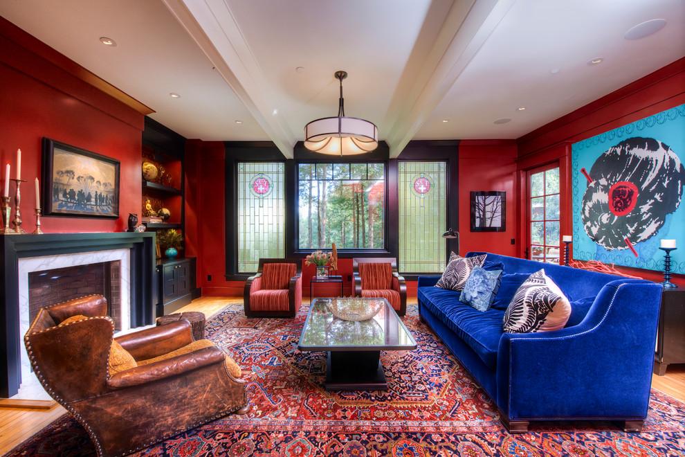 Foto de salón para visitas cerrado, contemporáneo, grande, sin televisor, con paredes rojas, suelo de madera en tonos medios, chimenea tradicional y marco de chimenea de piedra