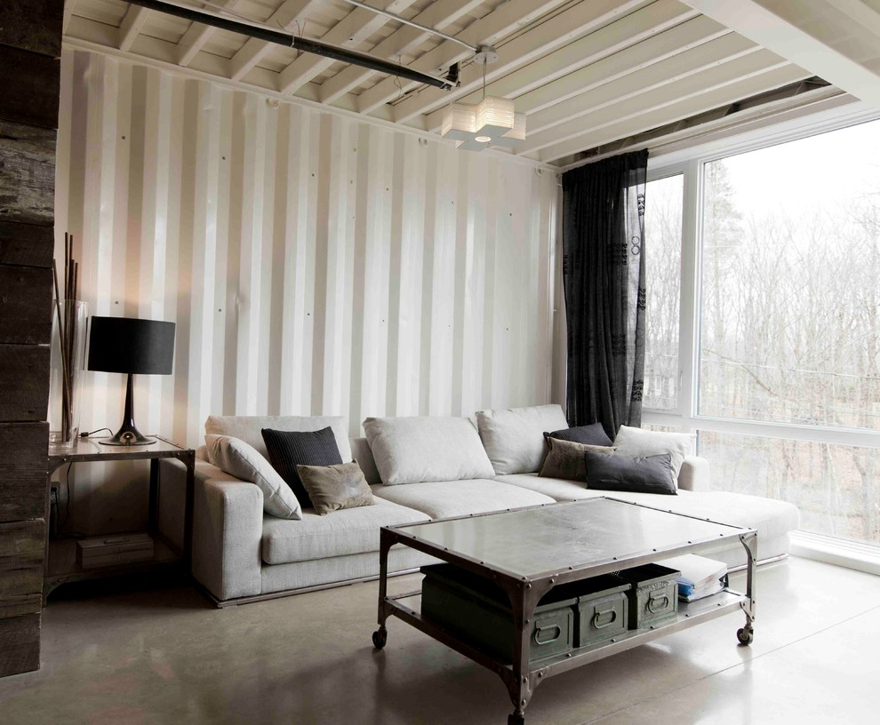 Urban concrete floor living room photo in Montreal with white walls