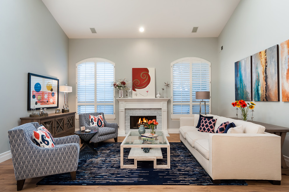 Living room - large coastal open concept light wood floor and multicolored floor living room idea in Los Angeles with gray walls, a standard fireplace and a stone fireplace