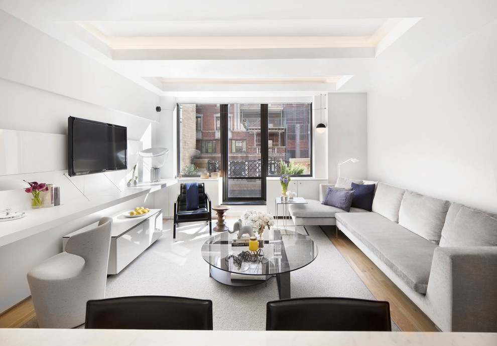 Living room - small contemporary formal and enclosed light wood floor and beige floor living room idea in New York with white walls, a wall-mounted tv and no fireplace