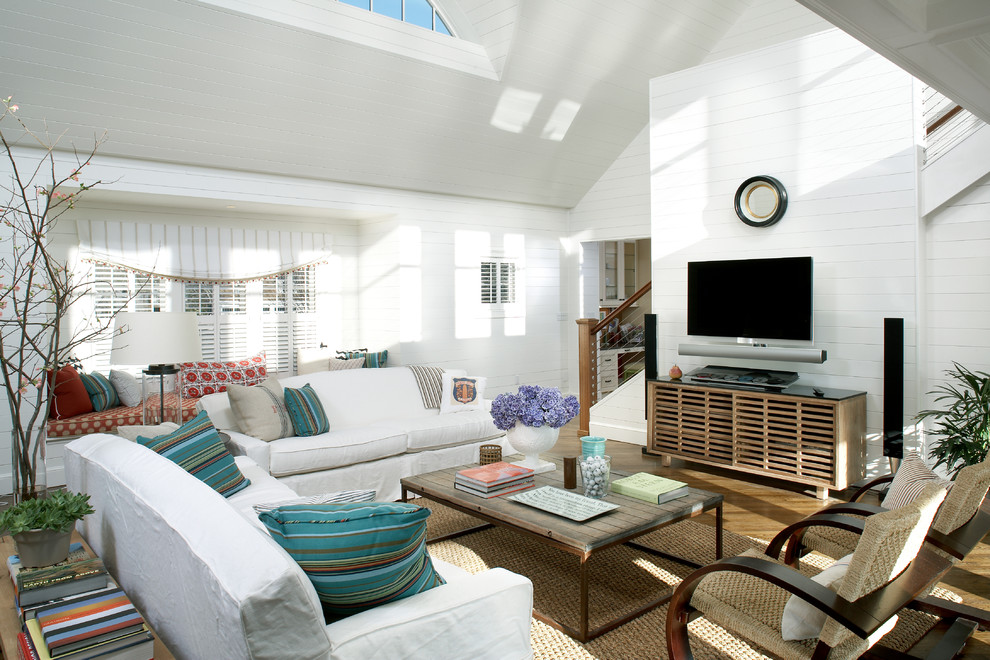 Large beach style open concept medium tone wood floor living room photo in Boston with white walls and a wall-mounted tv