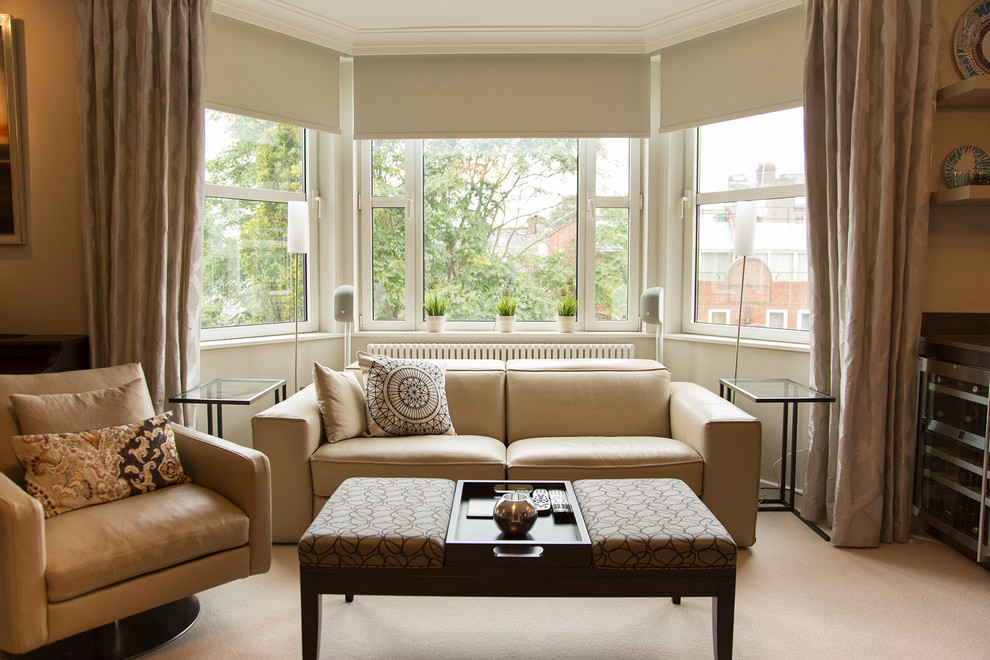 Inspiration for a mid-sized contemporary open concept carpeted living room remodel in London with beige walls and no fireplace
