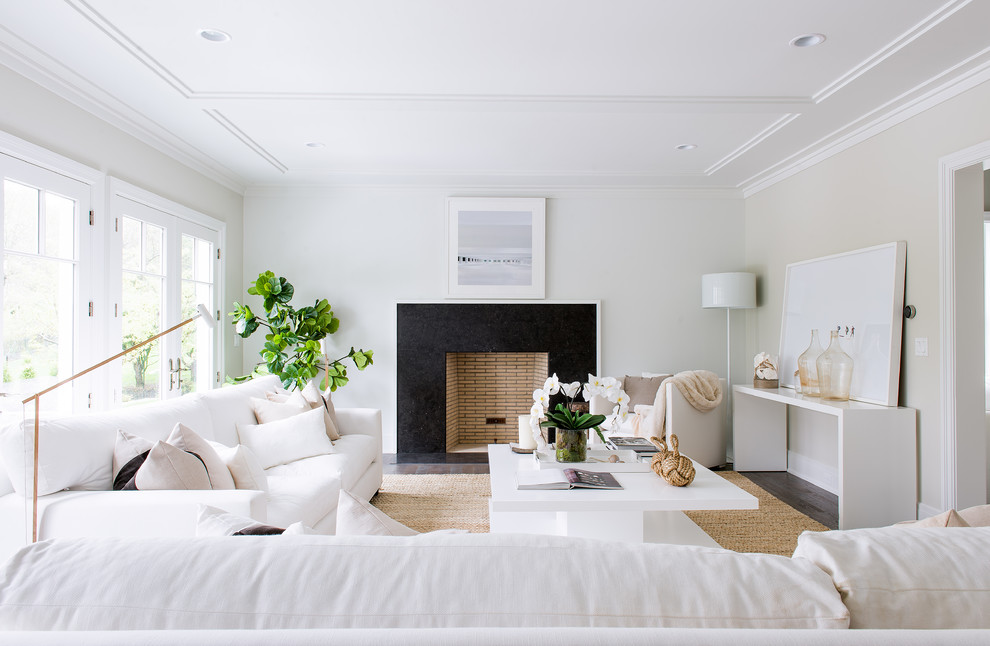 Example of a beach style formal living room design in New York with beige walls, a standard fireplace and no tv