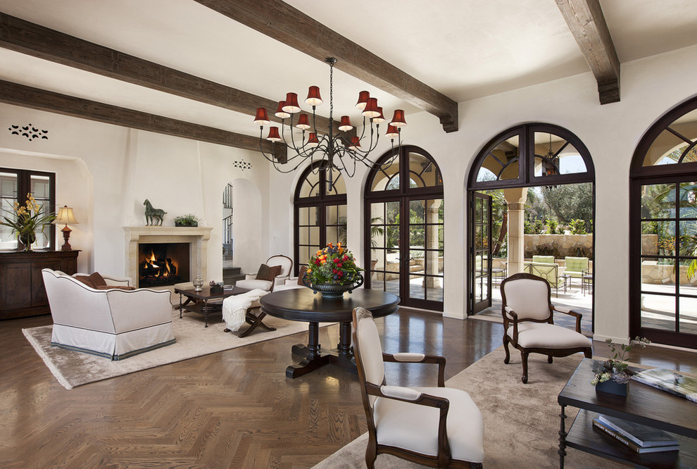 Inspiration for a mediterranean formal medium tone wood floor living room remodel in Santa Barbara with beige walls, a standard fireplace and a stone fireplace
