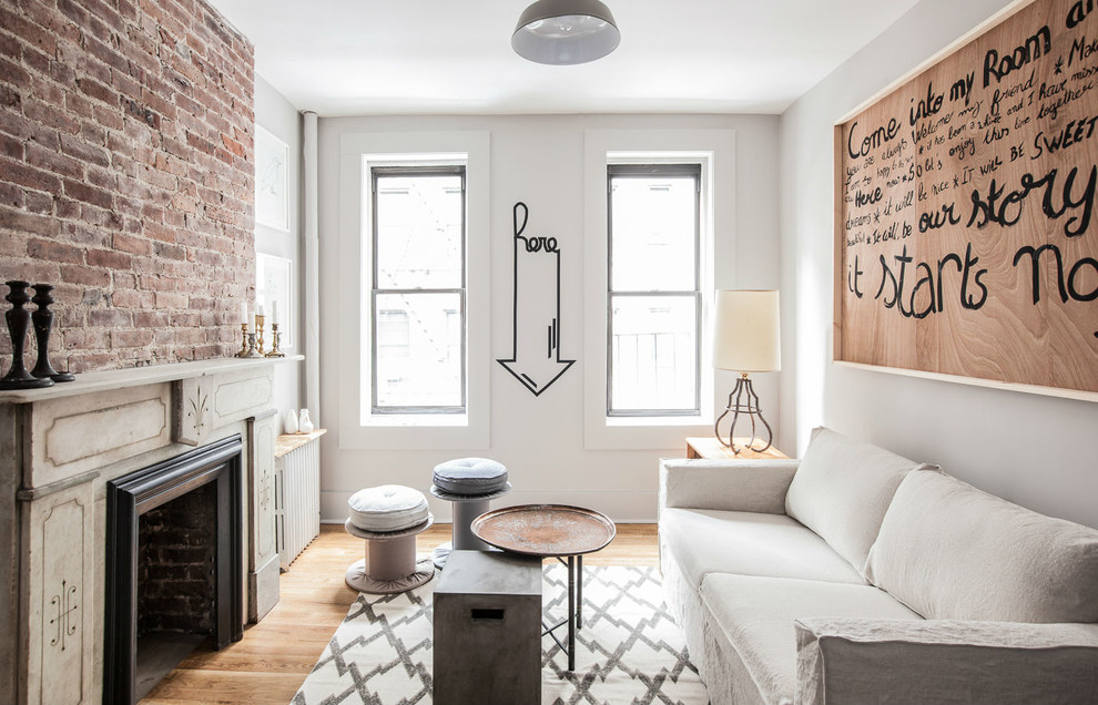 Small eclectic enclosed medium tone wood floor living room photo in New York with gray walls, a standard fireplace and no tv
