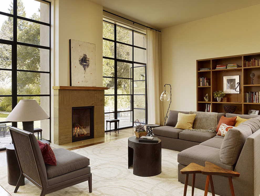 Example of a transitional living room design in San Francisco with a concrete fireplace