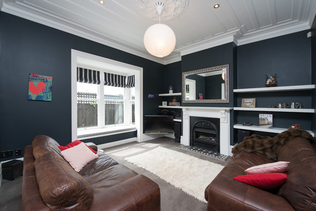 This is an example of a contemporary enclosed living room in Christchurch with blue walls, carpet, a standard fireplace, a plaster fireplace surround and a wall-mounted tv.