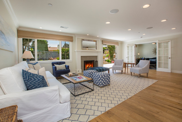 This is an example of a beach style living room in Santa Barbara with a standard fireplace, no tv and light hardwood floors.