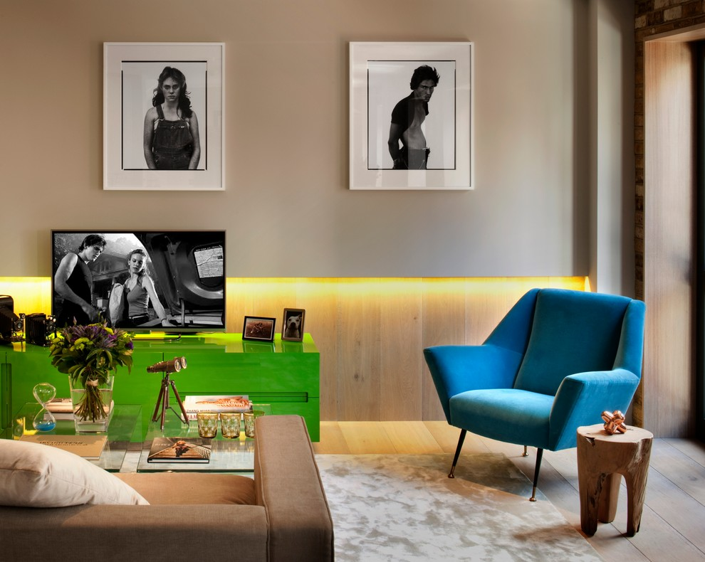 Mid-sized trendy light wood floor living room photo in London with beige walls and a tv stand