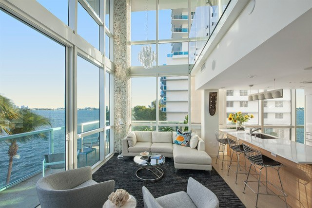 Example of a mid-sized trendy formal and loft-style porcelain tile living room design in Miami with white walls
