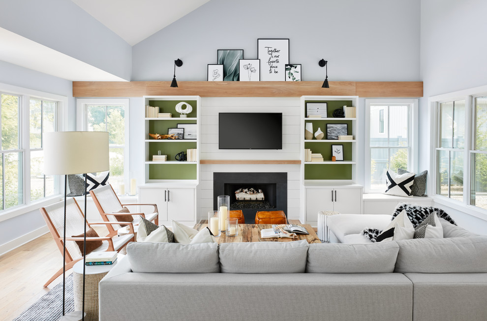 Beach style medium tone wood floor and brown floor living room photo in Chicago with blue walls, a standard fireplace and a wall-mounted tv