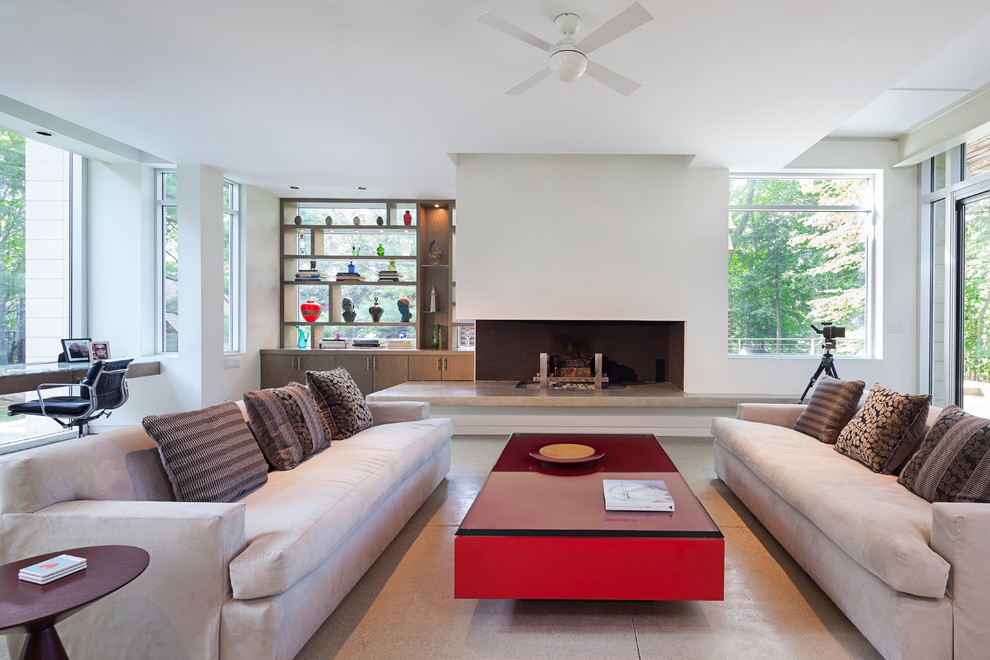 Large minimalist open concept concrete floor living room photo in Grand Rapids with white walls, a two-sided fireplace and a plaster fireplace