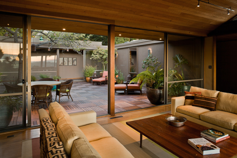Example of a large trendy open concept medium tone wood floor living room design in San Francisco with beige walls