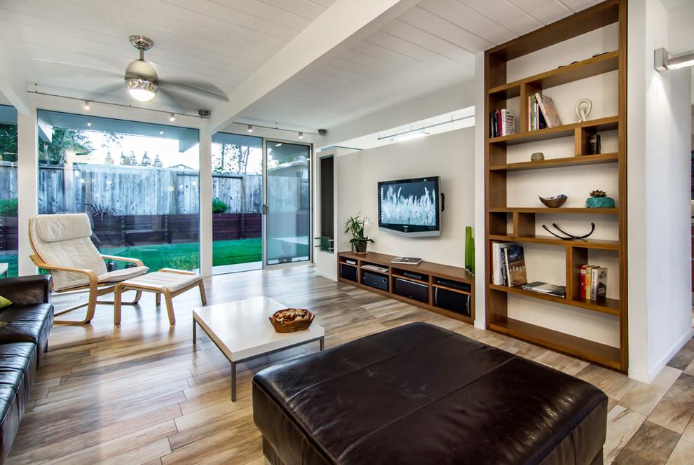 Immagine di un soggiorno moderno di medie dimensioni e aperto con pareti bianche, TV a parete, libreria, pavimento in gres porcellanato e pavimento beige