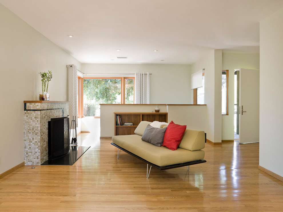 Inspiration for a mid-sized modern formal and enclosed medium tone wood floor and beige floor living room remodel in Portland with white walls, a standard fireplace, a tile fireplace and no tv