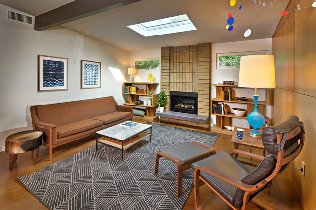 Example of a mid-sized 1960s open concept concrete floor and brown floor living room library design in Sacramento with white walls, a standard fireplace, a brick fireplace and a media wall
