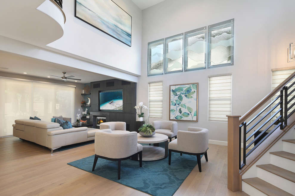 Living room - large coastal open concept light wood floor and beige floor living room idea in Orange County with a media wall
