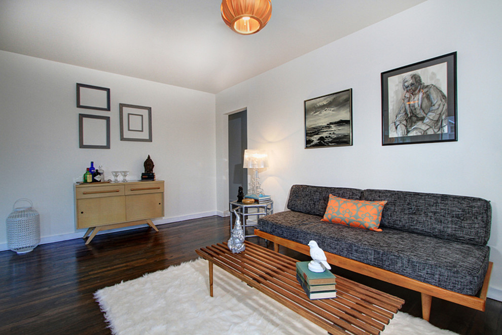 Example of a minimalist enclosed dark wood floor living room design in Los Angeles with white walls