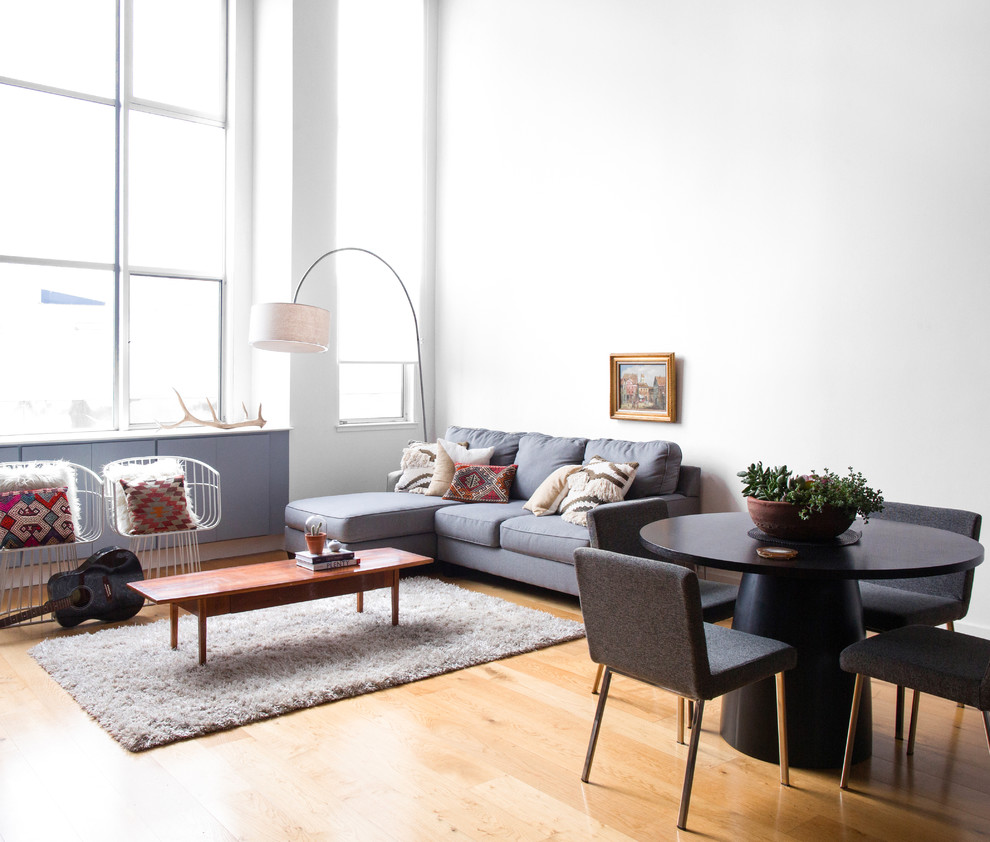 Large danish open concept light wood floor and beige floor living room photo in New York with white walls, a standard fireplace and a metal fireplace