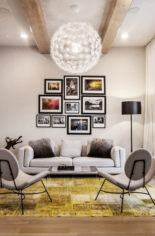 Example of a trendy medium tone wood floor, brown floor and exposed beam living room design in Dallas with beige walls