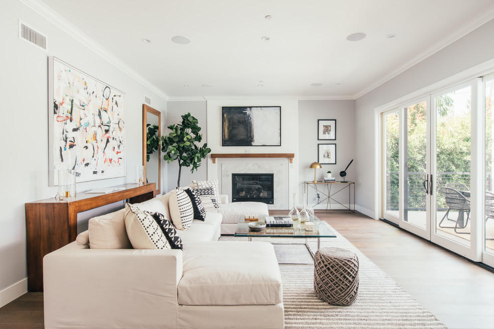 Example of a beach style medium tone wood floor and brown floor living room design in Los Angeles with gray walls and a standard fireplace
