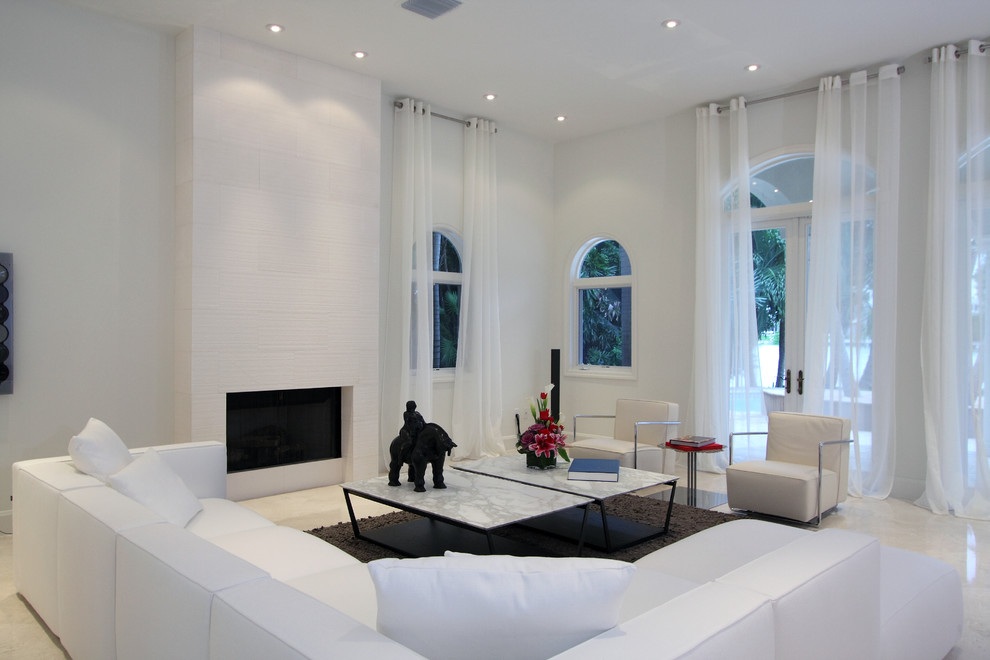 Trendy marble floor living room photo in Miami with white walls and a standard fireplace