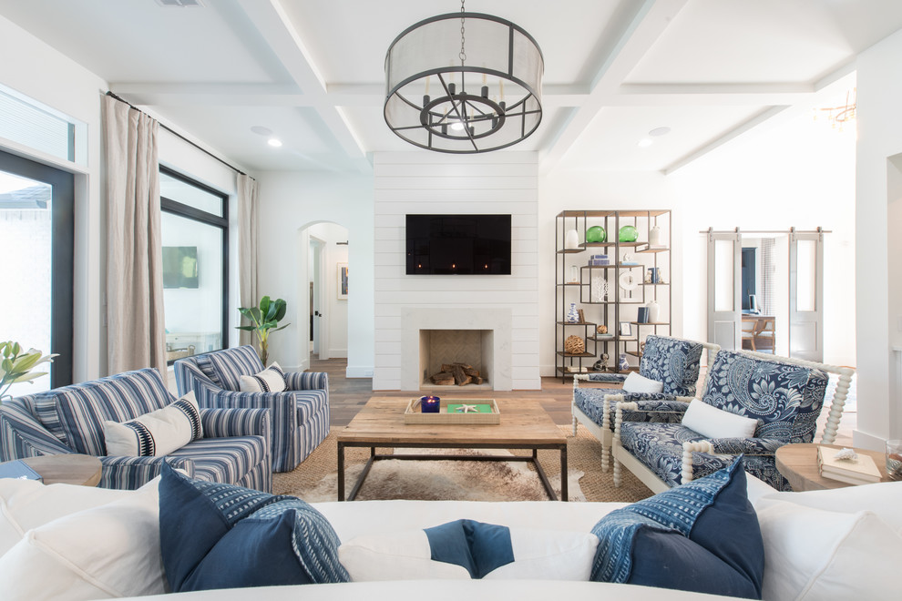 Example of a beach style dark wood floor and brown floor living room design in Houston with white walls and a standard fireplace