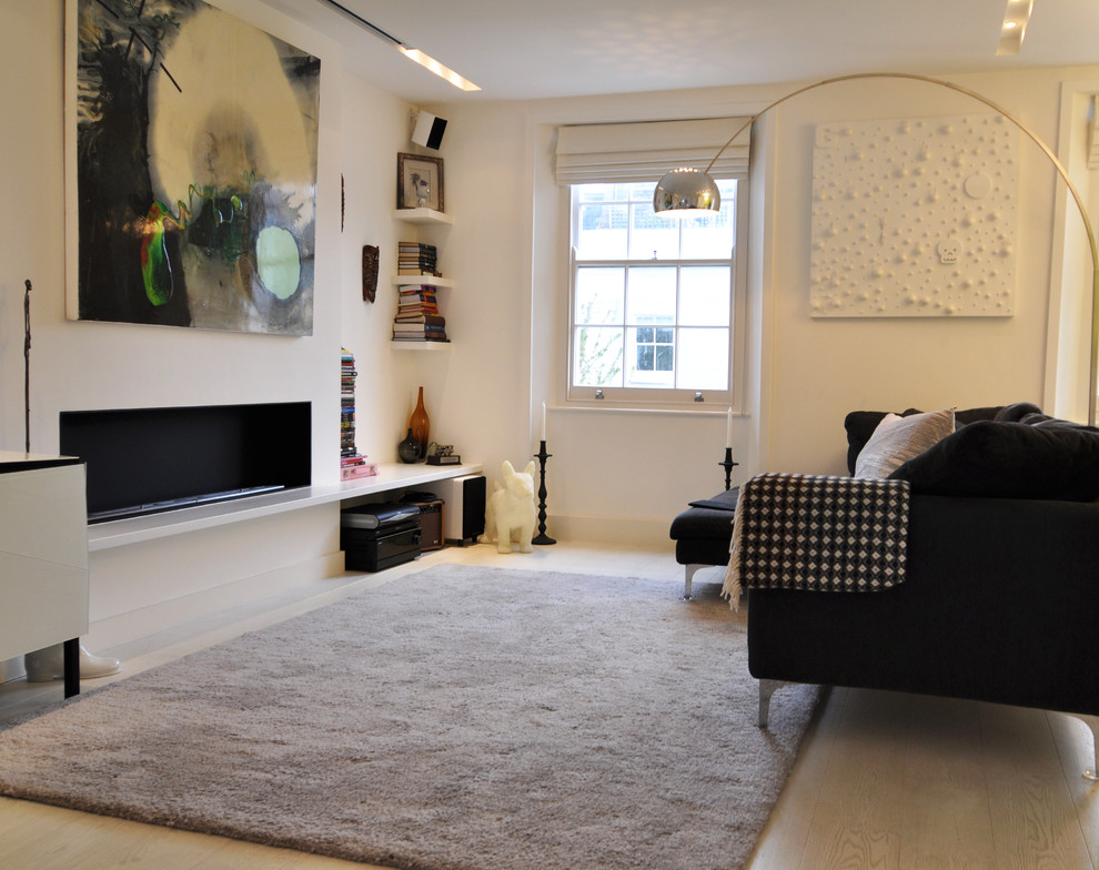 Mid-sized danish light wood floor living room photo in London with white walls and a ribbon fireplace