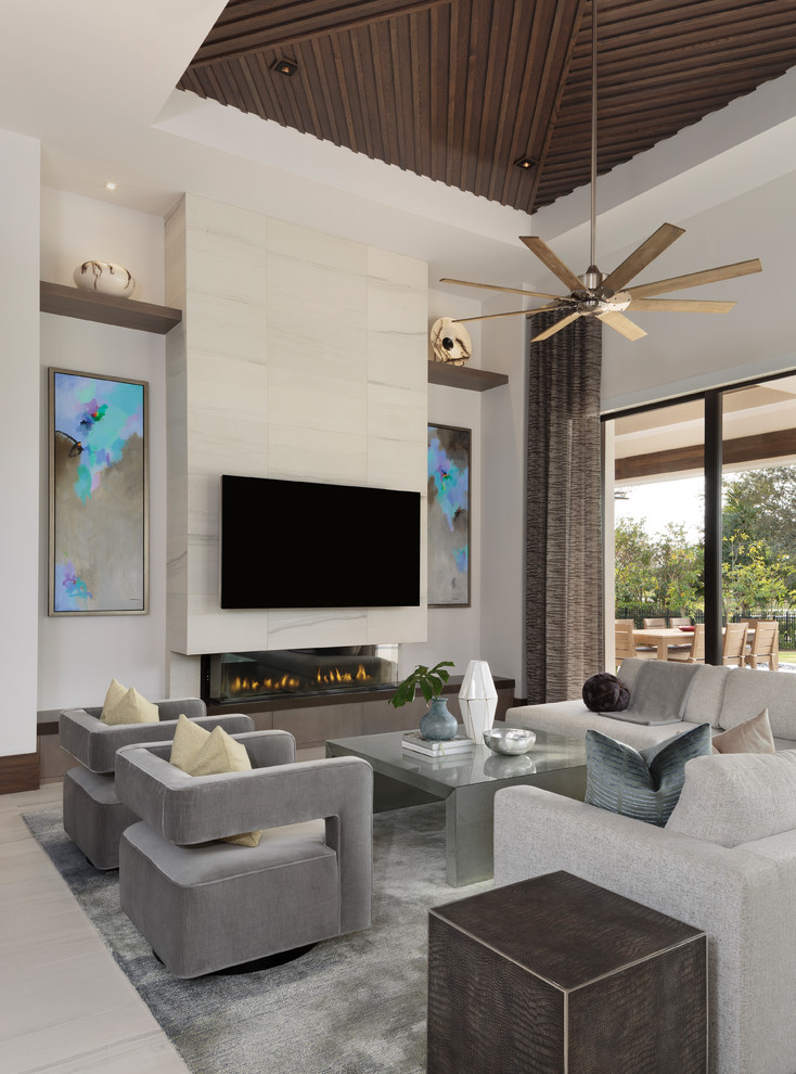 Example of a large minimalist open concept porcelain tile and beige floor living room design in Miami with white walls, a ribbon fireplace, a wall-mounted tv and a tile fireplace