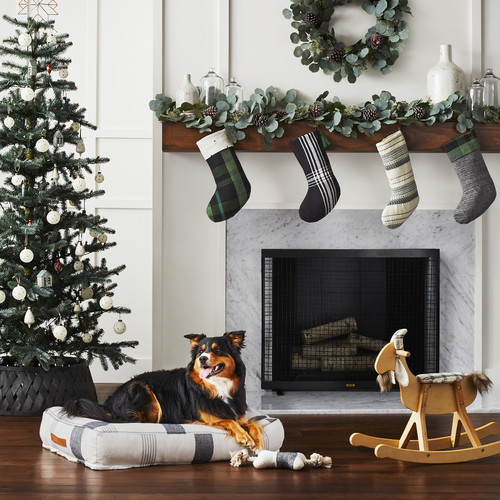 Holiday Decor Ideas for Dog Lovers - Black and white dog lying on black and white bed in front of fireplace.  Christmas tree in background