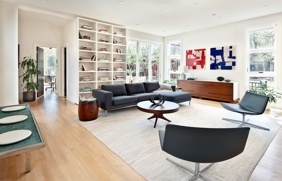 Example of a large minimalist open concept light wood floor living room design in Los Angeles with white walls and a media wall