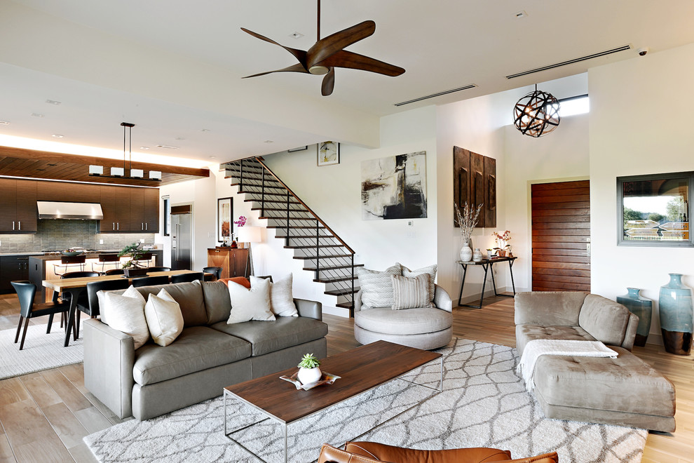 Living room - mid-sized modern open concept medium tone wood floor and gray floor living room idea in Dallas with white walls, a standard fireplace, a stone fireplace and a media wall