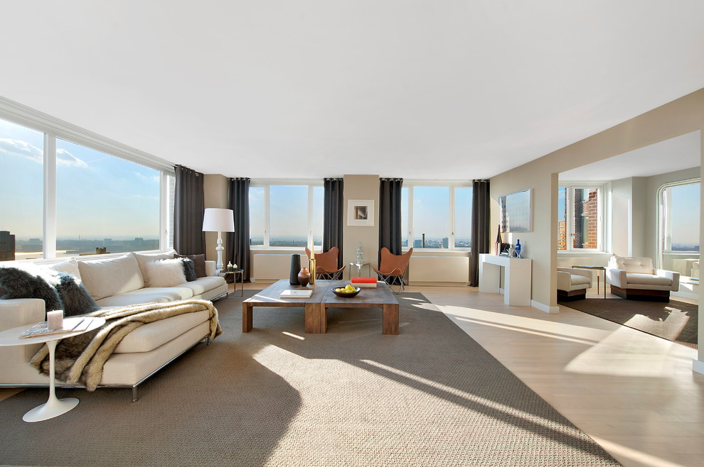 Example of a huge minimalist living room design in New York with beige walls