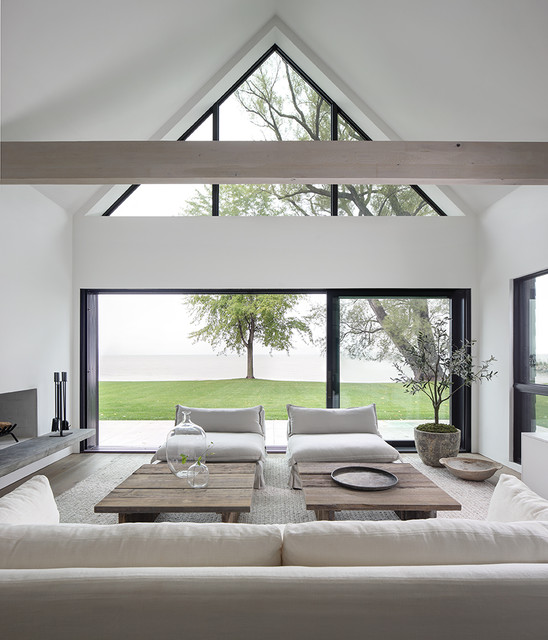 Example of a minimalist open concept light wood floor living room design in Milwaukee with white walls, a standard fireplace and a plaster fireplace